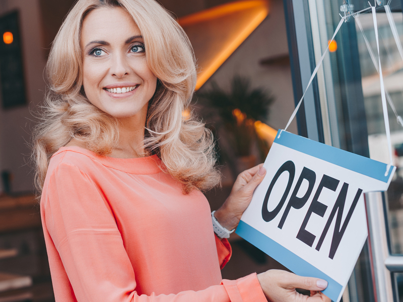 business woman holding an open signage