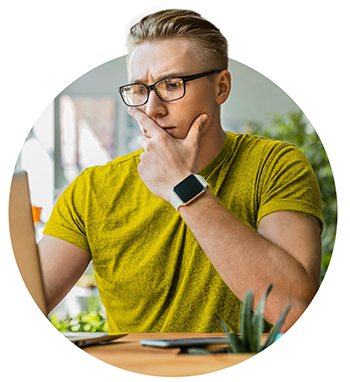 Concentrated young modern businessman analyzing data using laptop while sitting in the office