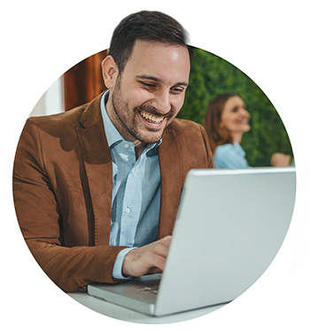smiling businessman working on laptop in the office.