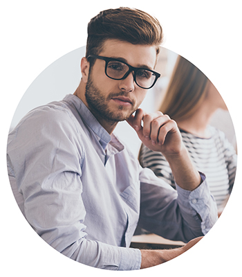 man with eyeglasses looking at camera while sitting at the office table on business meeting with his coworkers
