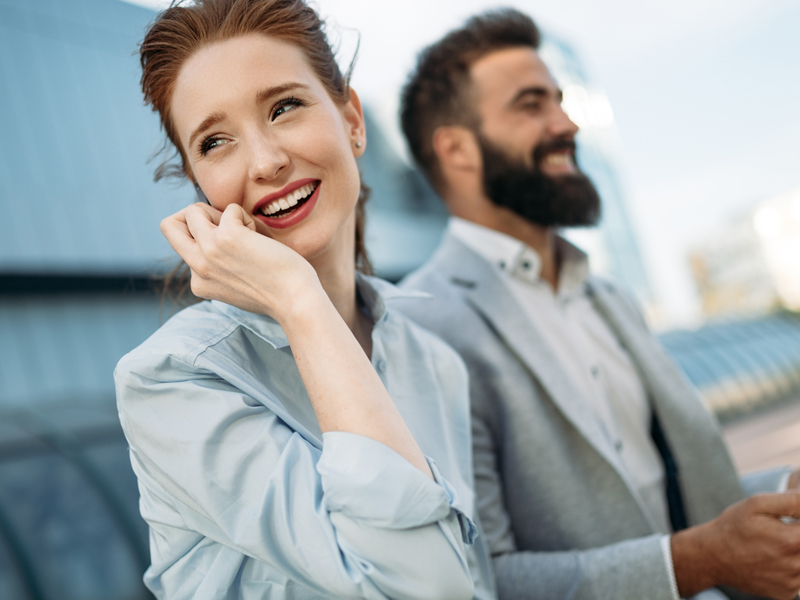 man and woman in business attire smiling