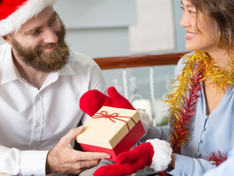 man giving Christmas gift to a woman