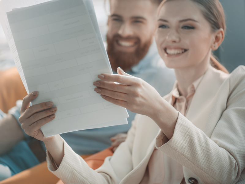 two people looking at a paper while smiling