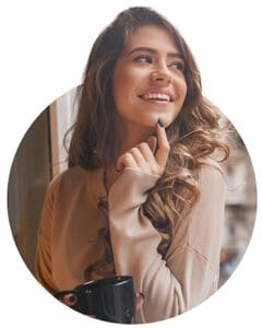 Pretty white woman playfully touching chin with finger while looking at city. Indoor photo of laughing romantic girl with cup of coffee standing near window..