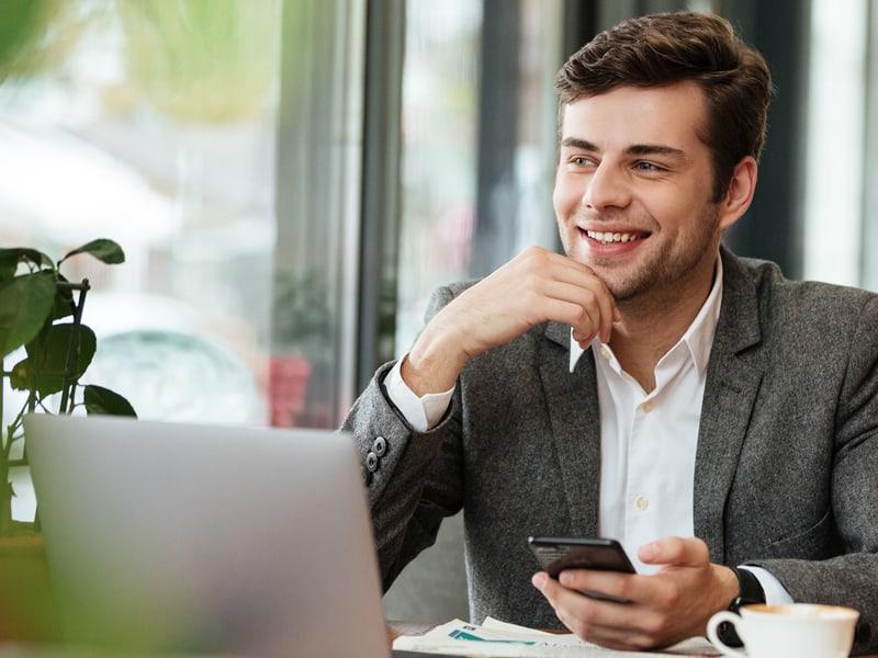 man smiling while looking at laptop